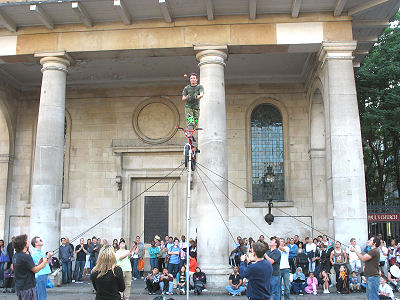 Street performer juggles knives and an apple. Fred is facing away from the camera, holding the rope just to the right of the pole.